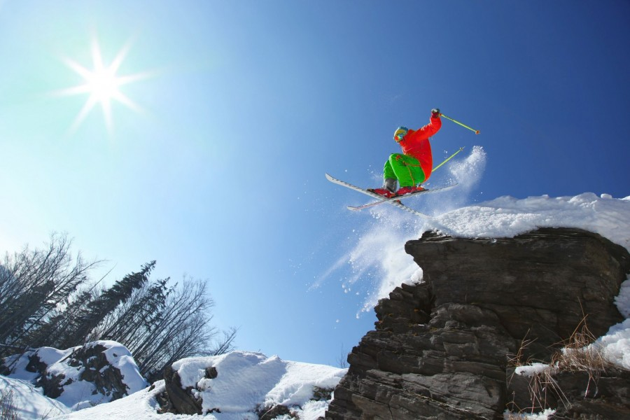 Skier jumping though the air from the cliff in high mountains