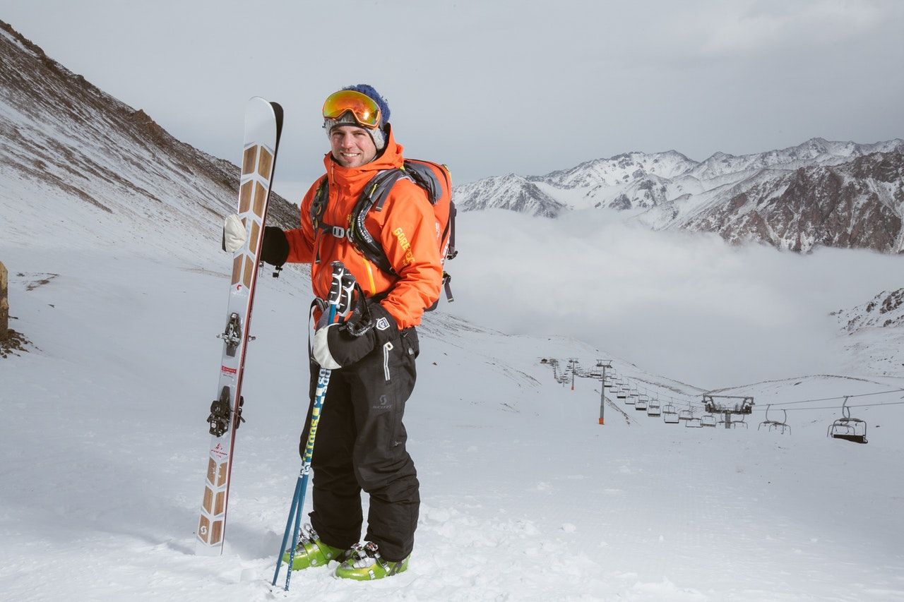 Man wearing orange and black snowsuit with ski set on snow