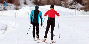 a man and a woman cross country skiing while wearing proper gear