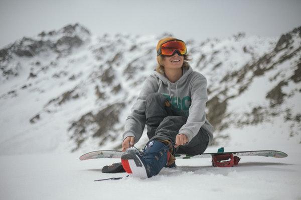 woman sitting on snowboard